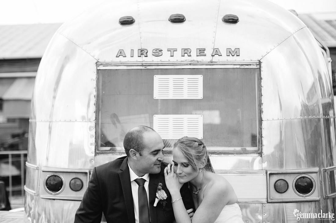 A bride and groom sitting in front of an Airstream caravan - The Theatre Bar at the End of the Wharf Wedding