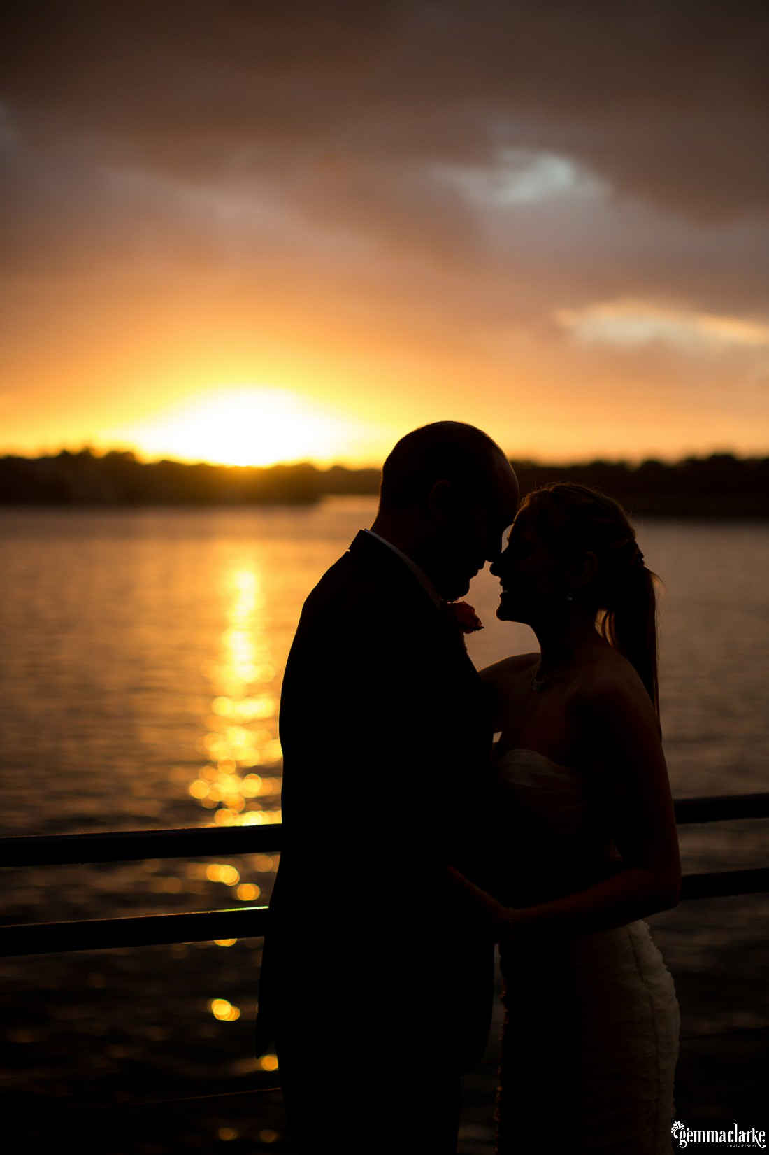 A silhouette of a bride and groom standing close near the water as the sun sets behind them - The Theatre Bar at the End of the Wharf Wedding