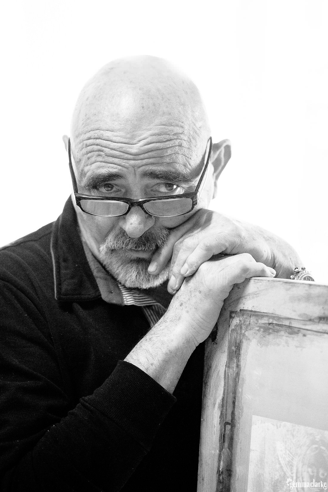 A black and white head and shoulder portrait of Elvio Marchionni leaning on the edge of a canvas looking over his glasses at the camera.
