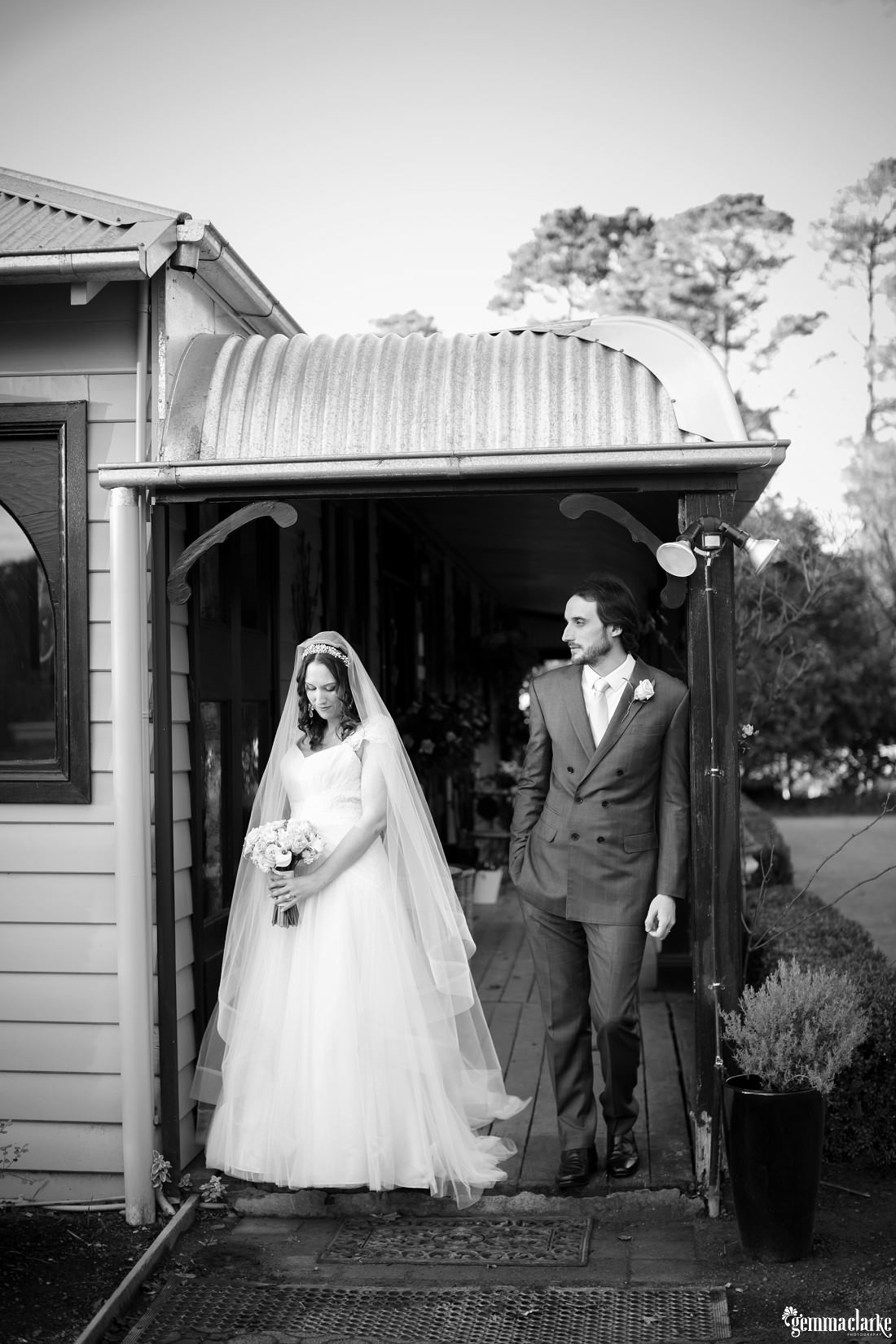A bride and groom standing on the verandah of a country homestead - Sylvan Glen Winter Wedding