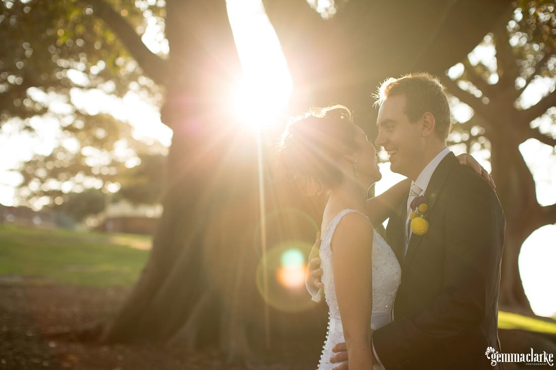 A smiling bride and groom embrace as the sun streams through a large tree behind them - Wedding in the Rocks