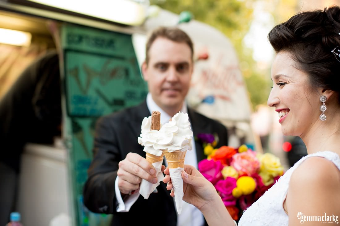 A bride and groom having an ice cream on their wedding day - Wedding in the Rocks
