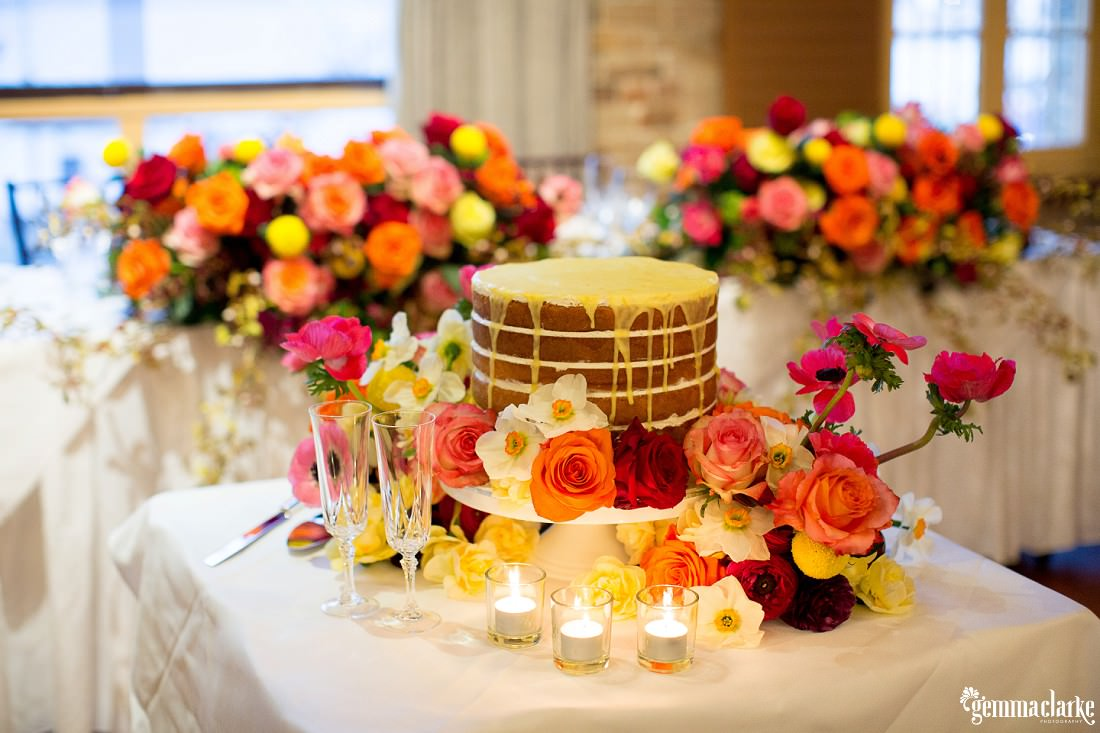 Wedding cake with floral decorations on a table with tea light candles - Wedding in the Rocks