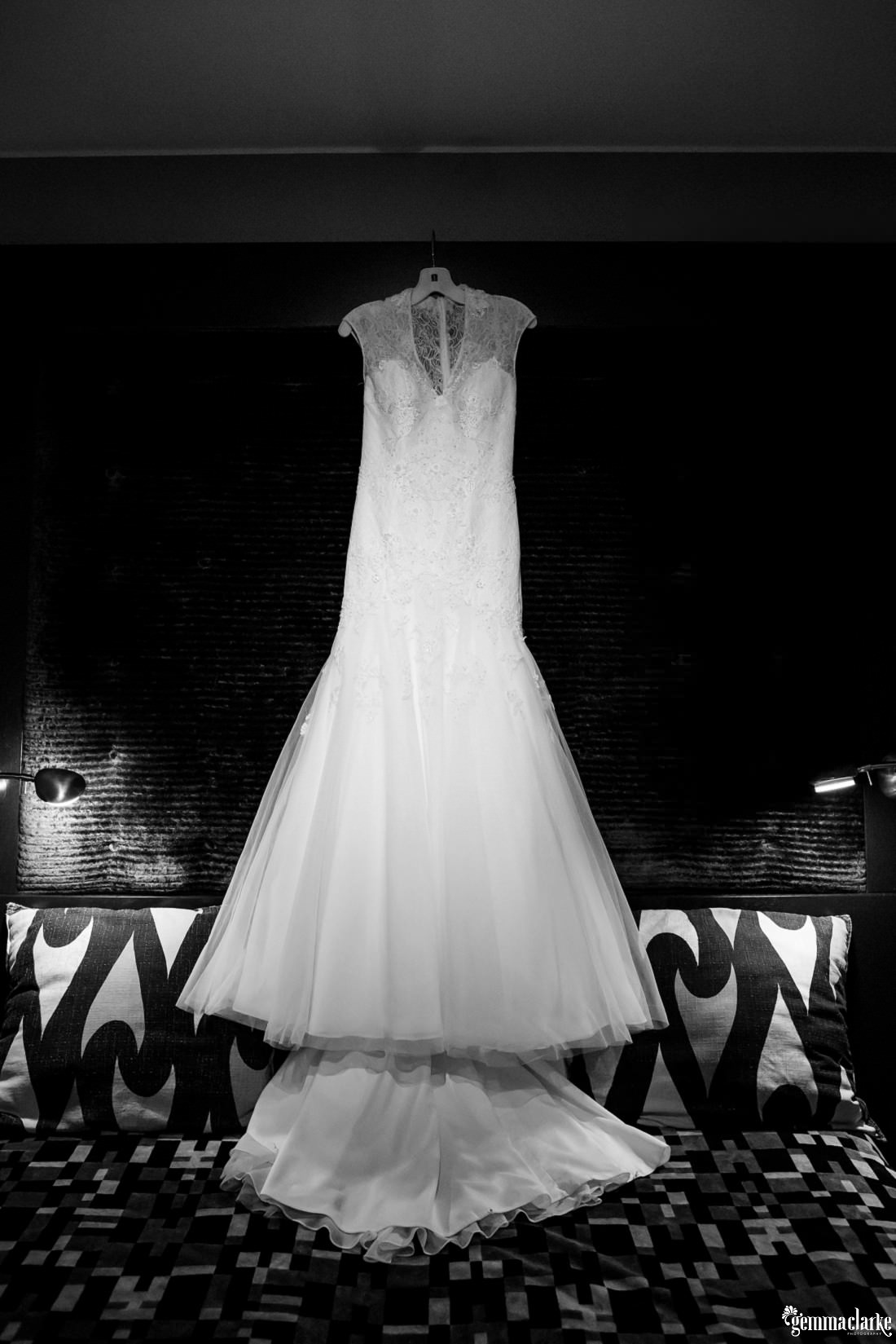 A white bridal gown hanging from a hanger over a bed