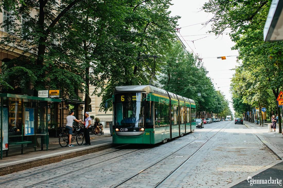 A tram on a tree line cobblestone street