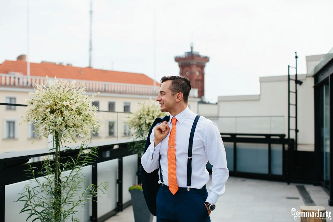 A smiling groom on a balcony holding his coat over one shoulder