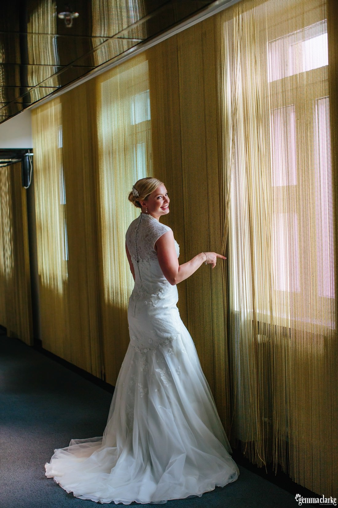 A smiling bride standing in front of a beaded curtain
