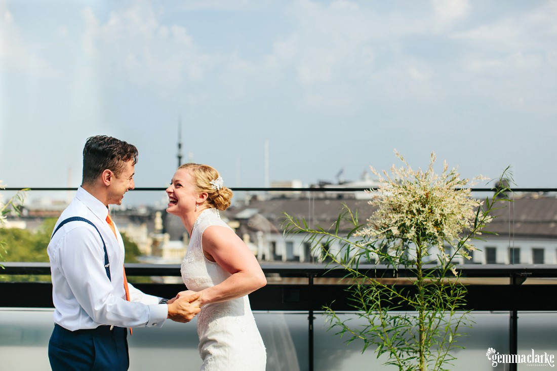 A bride and groom smile and hold hands on a rooftop terrace