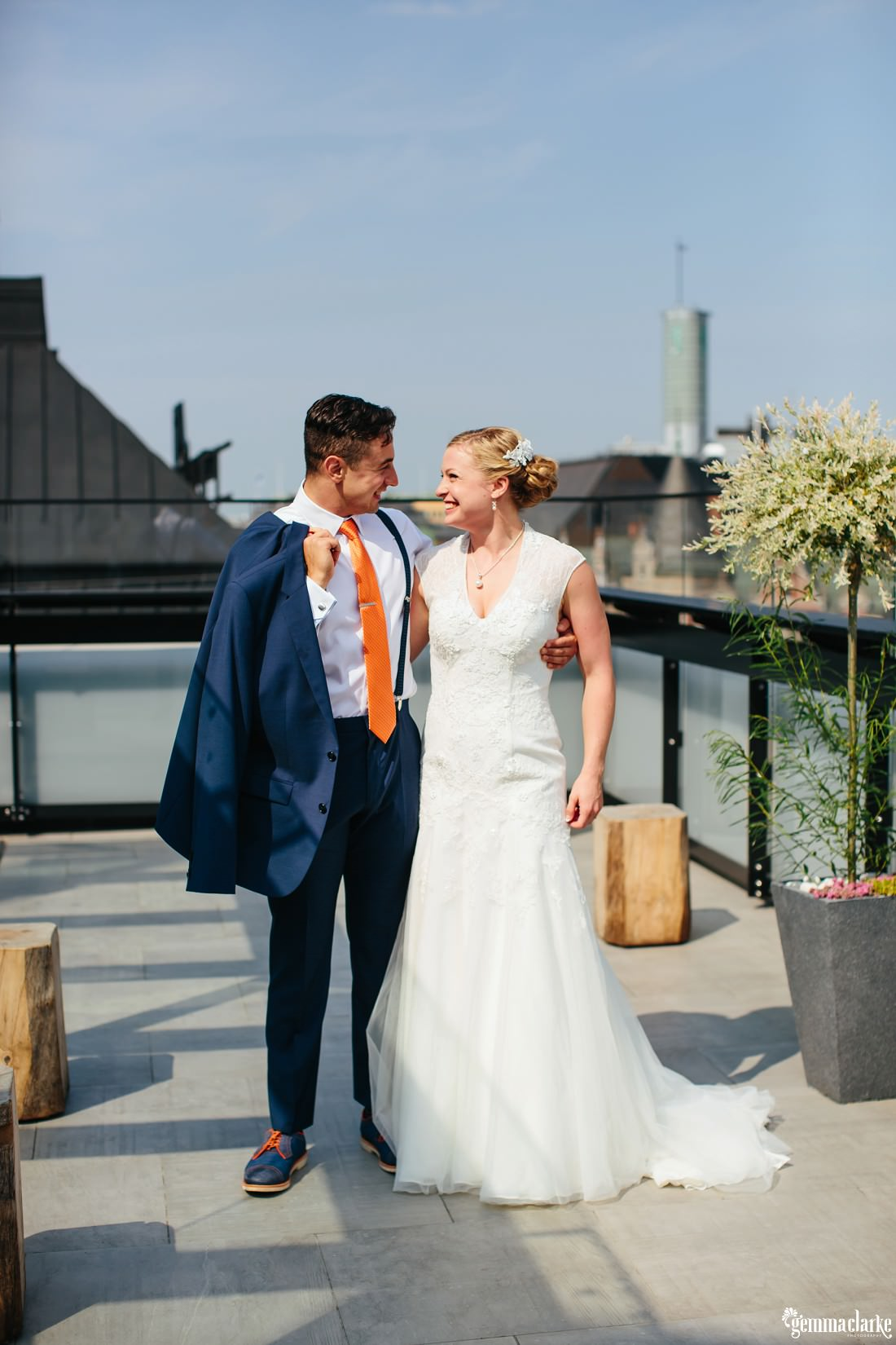 A smiling bride and groom with their arms around each other on a rooftop terrace