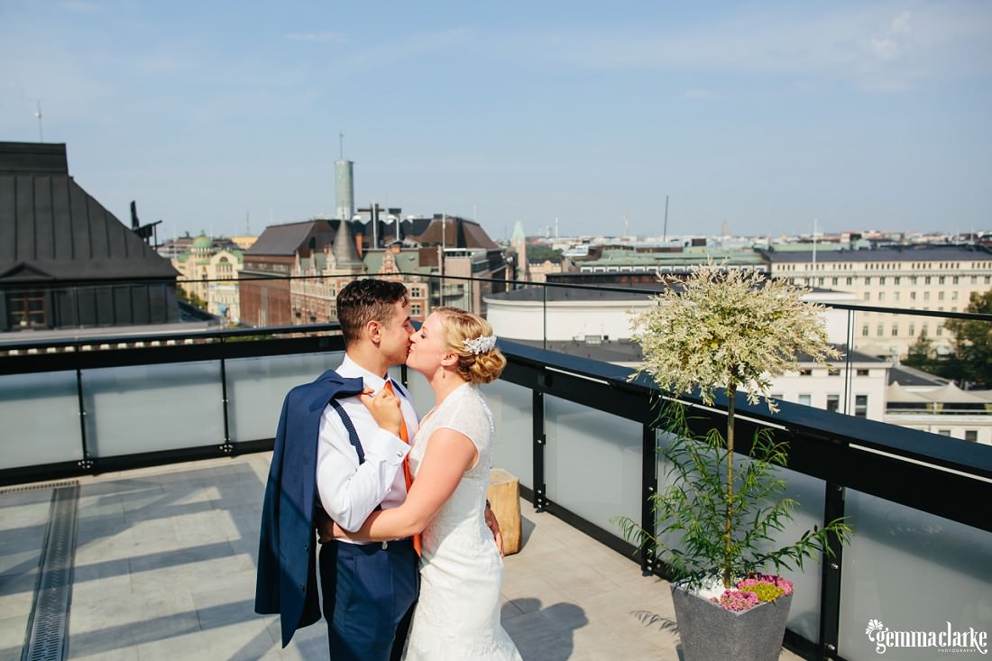 A bride and groom embracing and kissing on a rooftop
