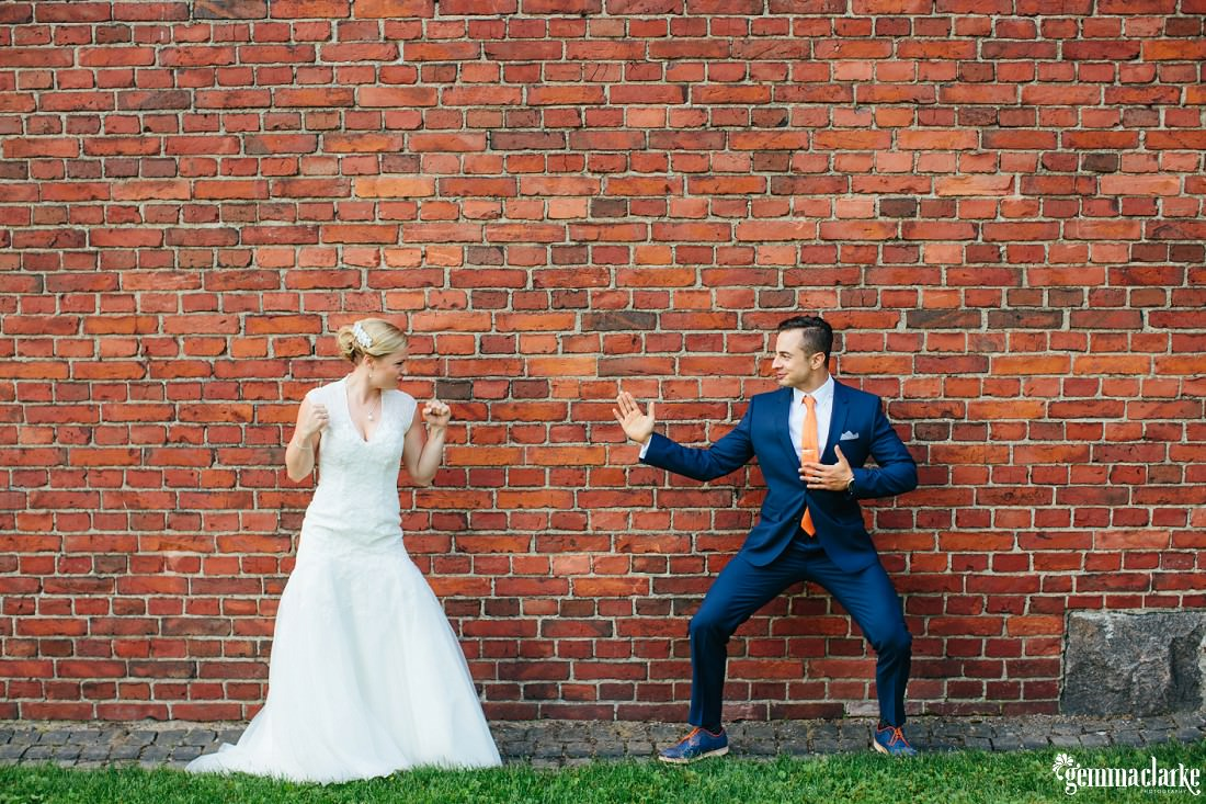 "A bride and groom in ""kung fu"" poses in front of a brick wall"