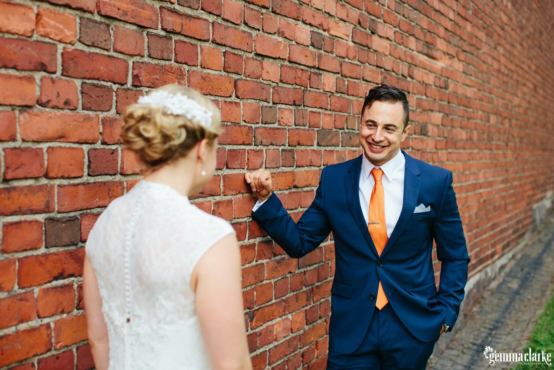 A groom leans against a brick wall and smiles at his bride