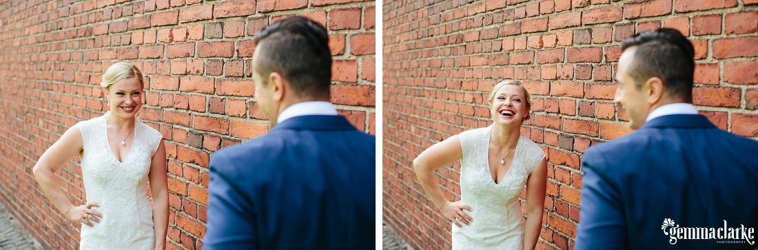 A bride smiling at her groom standing in front of a brick wall