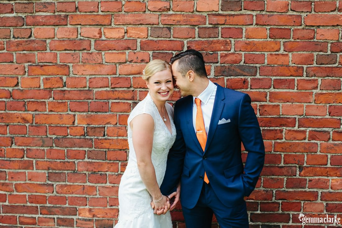 A groom nuzzles up to his smiling bride as they hold hands in front of a brick wall