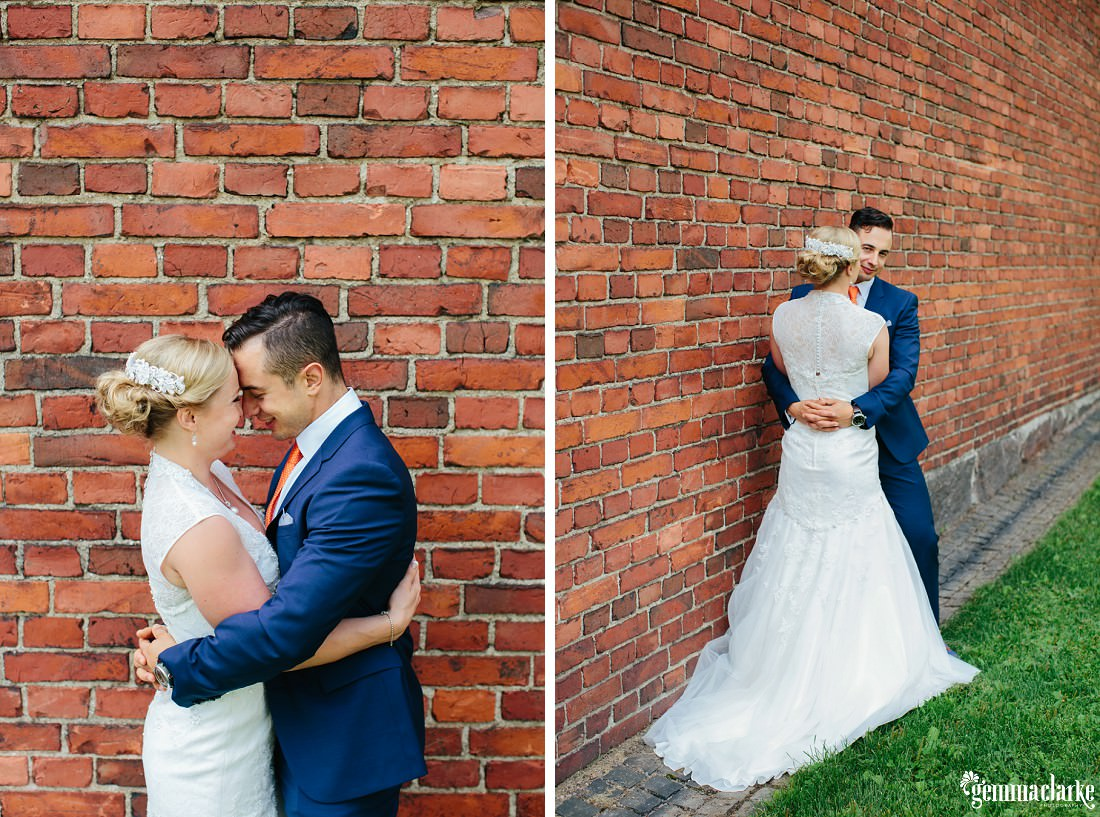 A bride and groom embrace in front of a brick wall