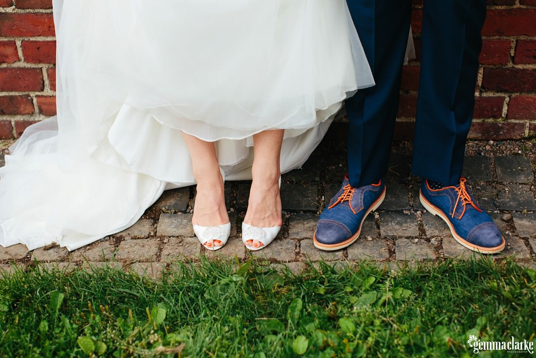 A close up of a bride and groom's shoes