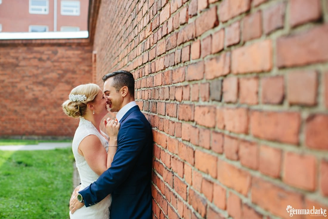 A bride and groom hold each other close against a brick wall