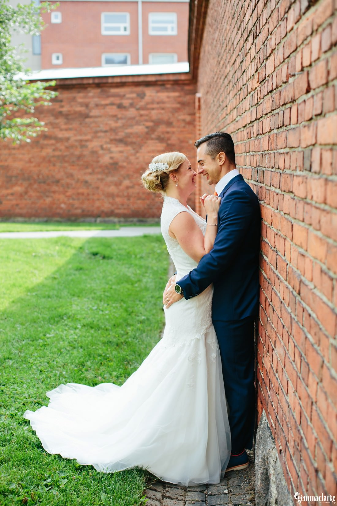 A bride and groom holding each other close against a brick wall
