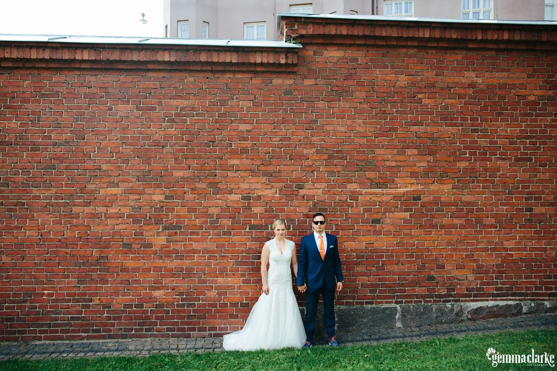 A bride and groom standing together and holding hands in front of a brick wall