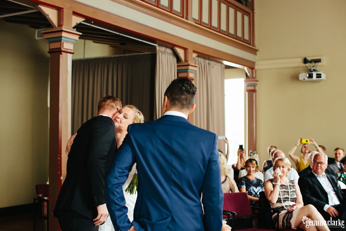 A bride getting a hug from her brother as he gives her away at her wedding as her groom looks on
