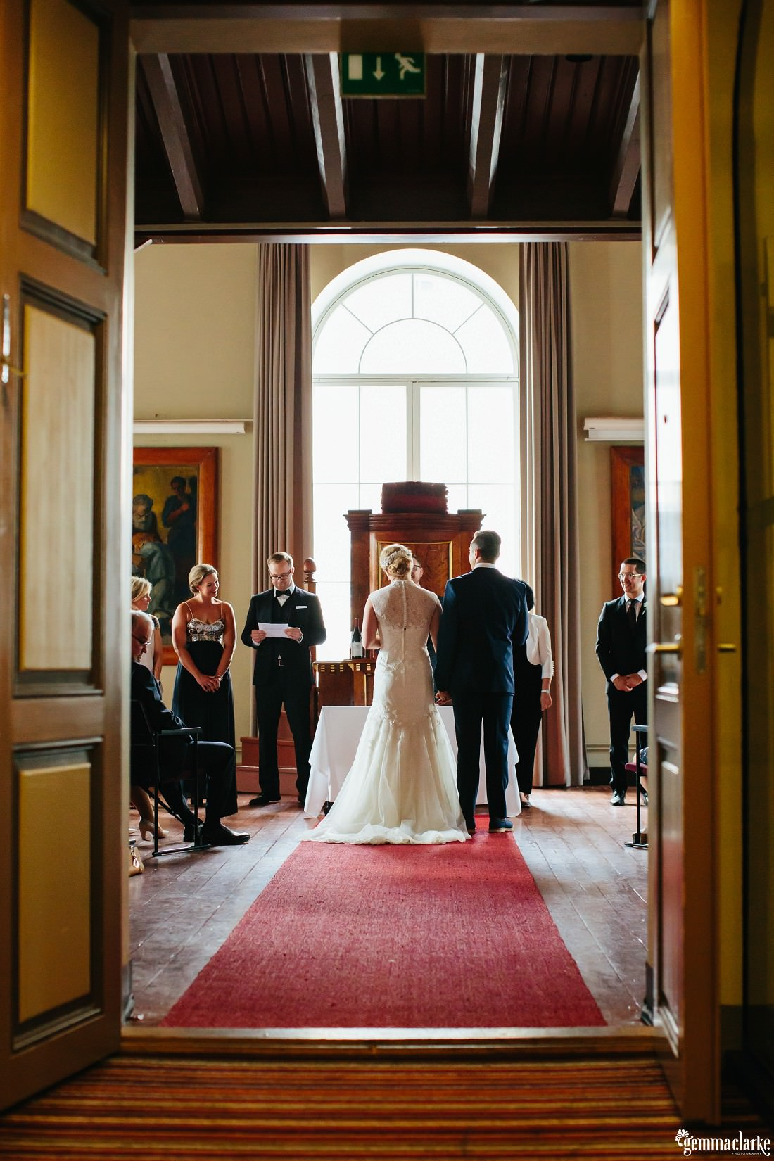 A wedding ceremony in progress as viewed through the entrance to the room