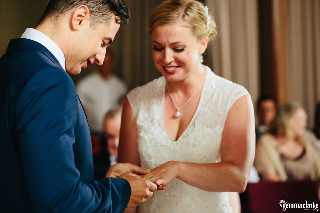 A groom puts a ring on the finger of his smiling bride