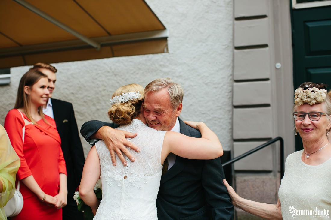 A bride getting a hug from a wedding guest