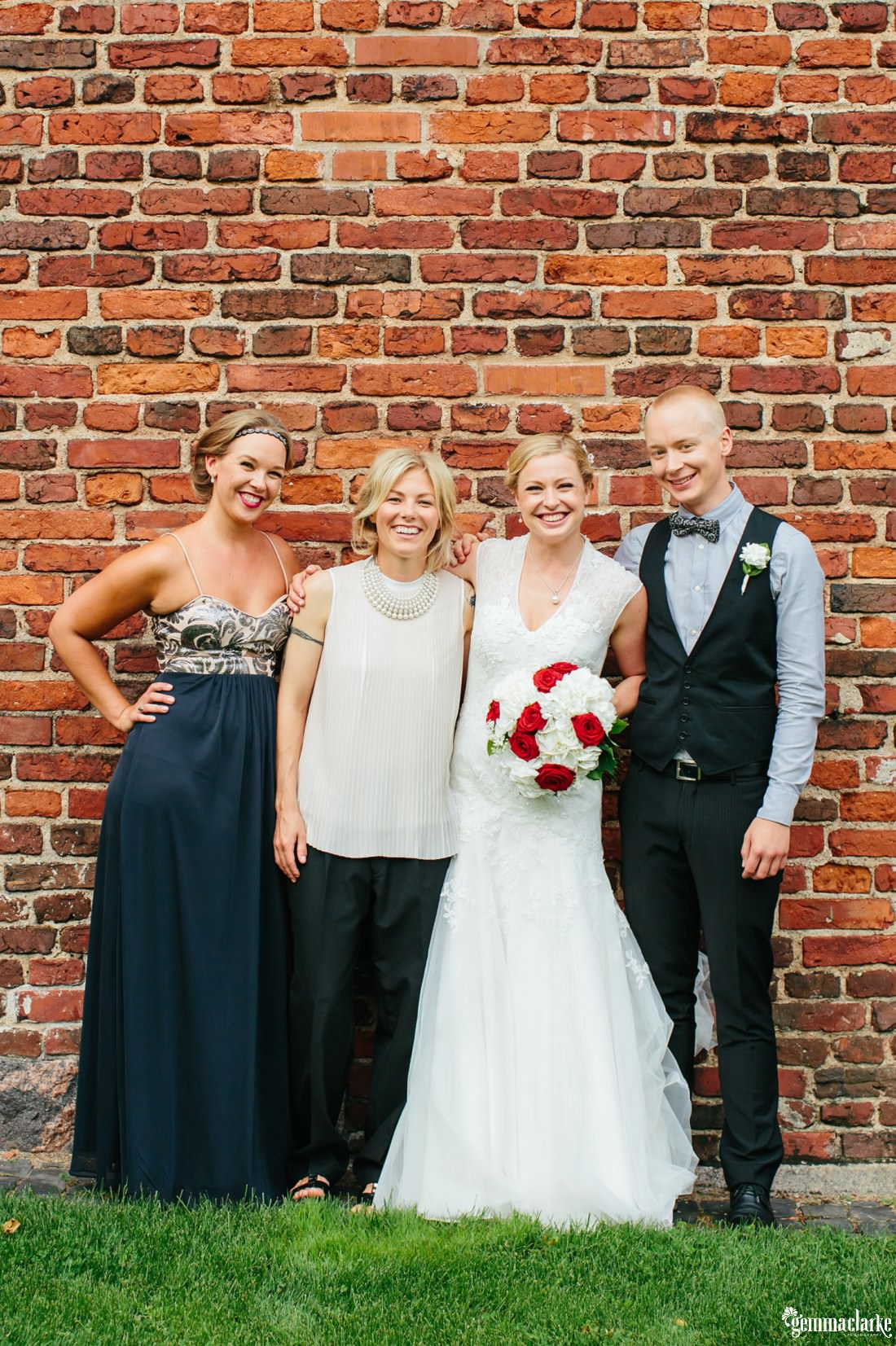 A bride poses with her bridal party in front of a brick wall
