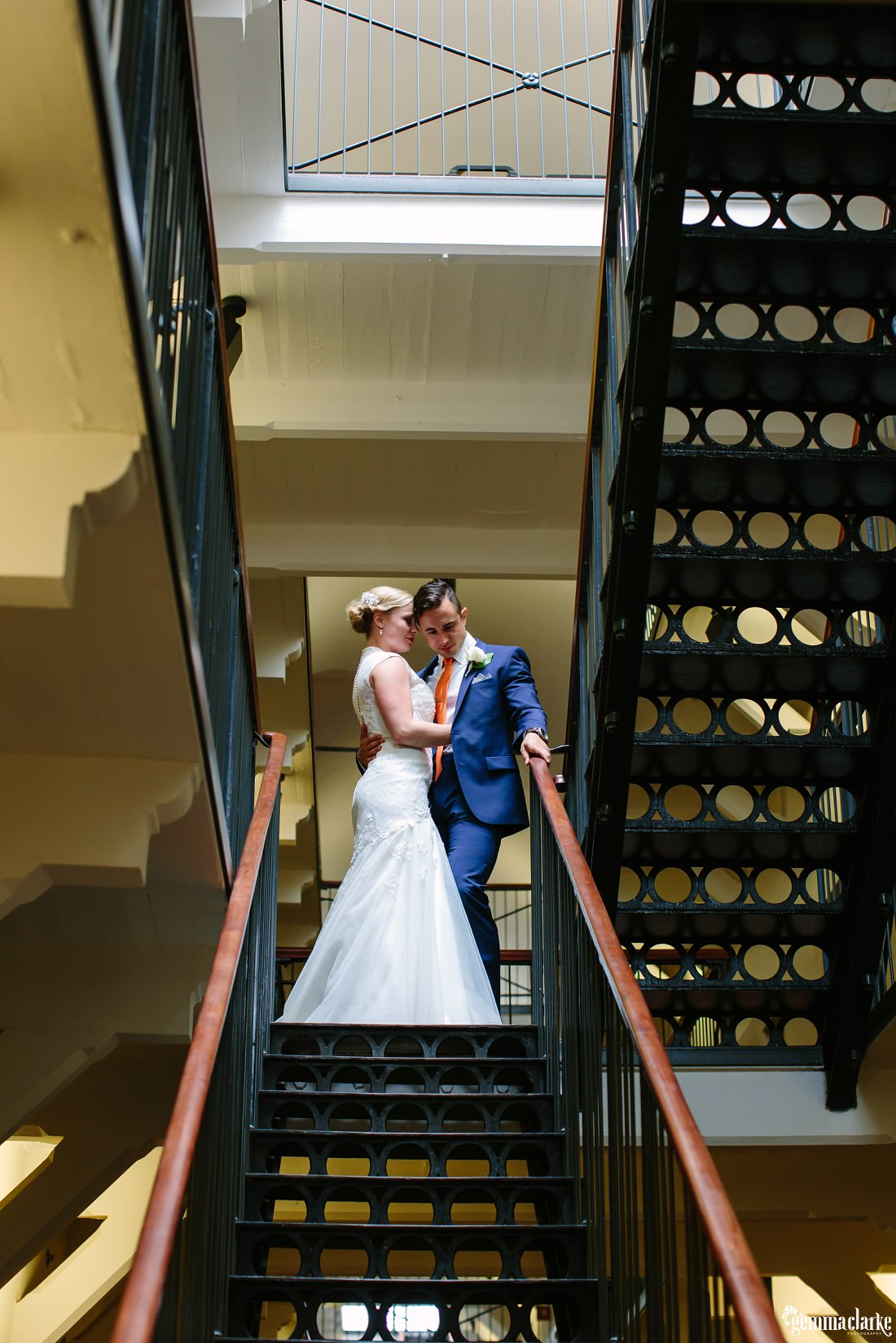 A groom holding his bride close as they stand at the top of a flight of stairs