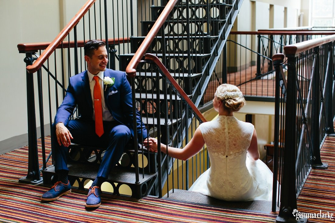 A groom smiles at his bride as they hold hands sitting on stairs