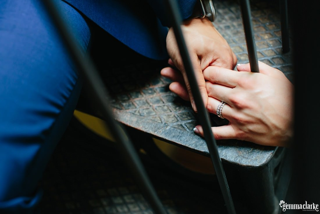 A bride and groom holding hands as they sit on stairs