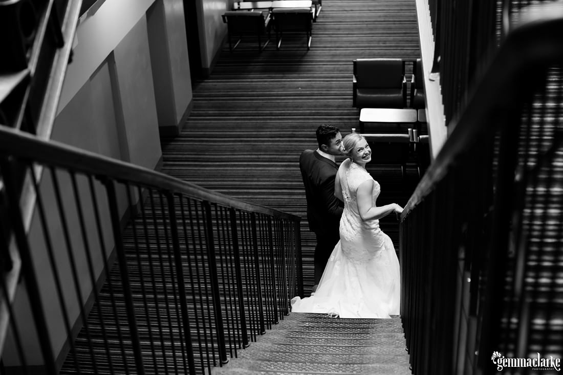 A bride smiles back over her shoulder as she and bride descend a flight of stairs