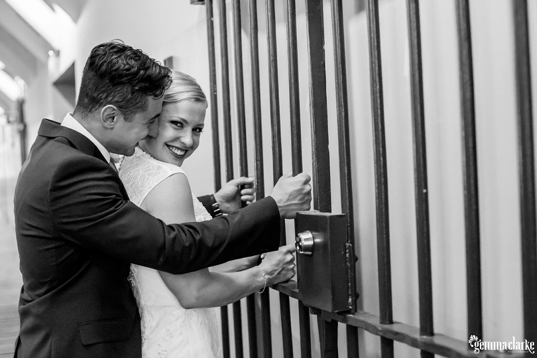 A groom nuzzles up to his bride from behind as they hold bars of an iron gate