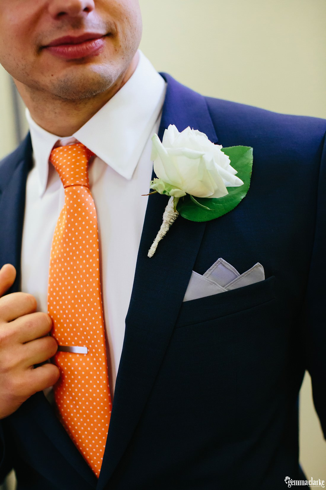 A close up of the details of a groom's attire including orange tie, tie bar and floral buttonhole