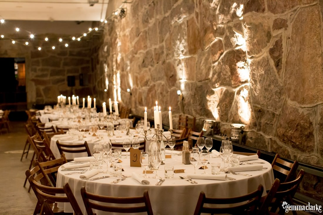 Wedding reception table setup with white table cloths, wooden chairs and candelabras in a room with stone walls