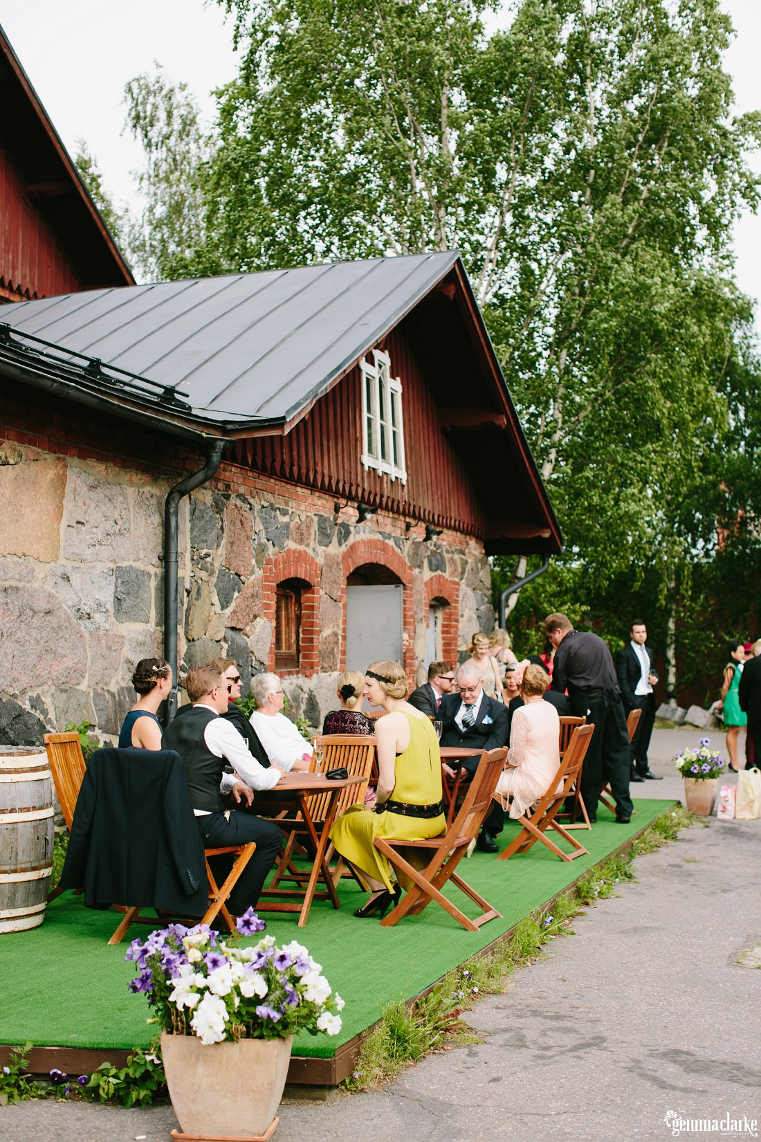 Wedding guests seated outside on wooden chairs