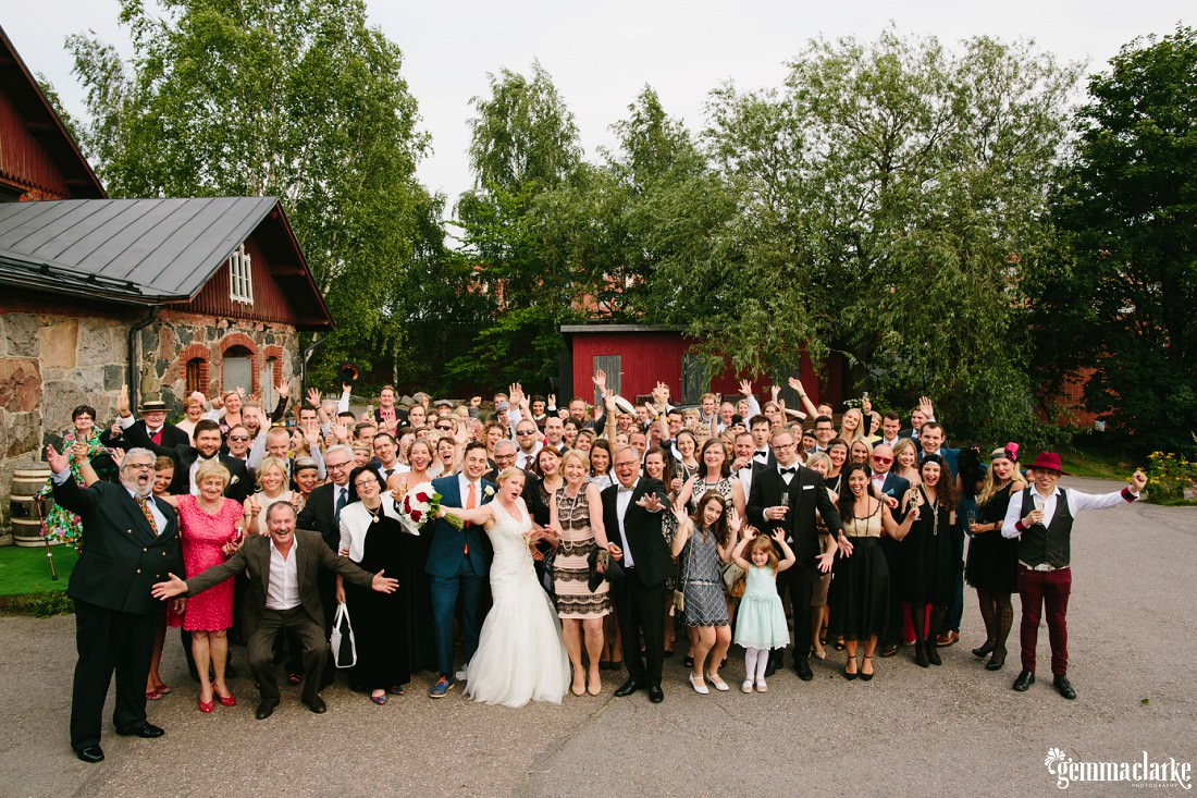 An outside group shot of a wedding party and their guests with their hands in the air