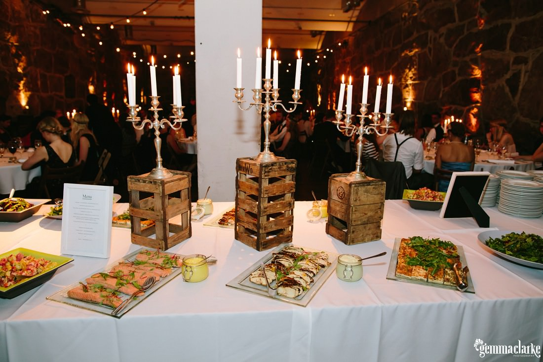 Various plates of food on a table with candelabras on small wooden crates with wedding guests seated in the background