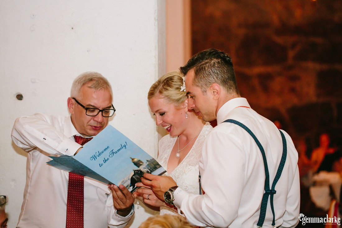 "A bride and groom being given a ""Welcome to the Family"" card"