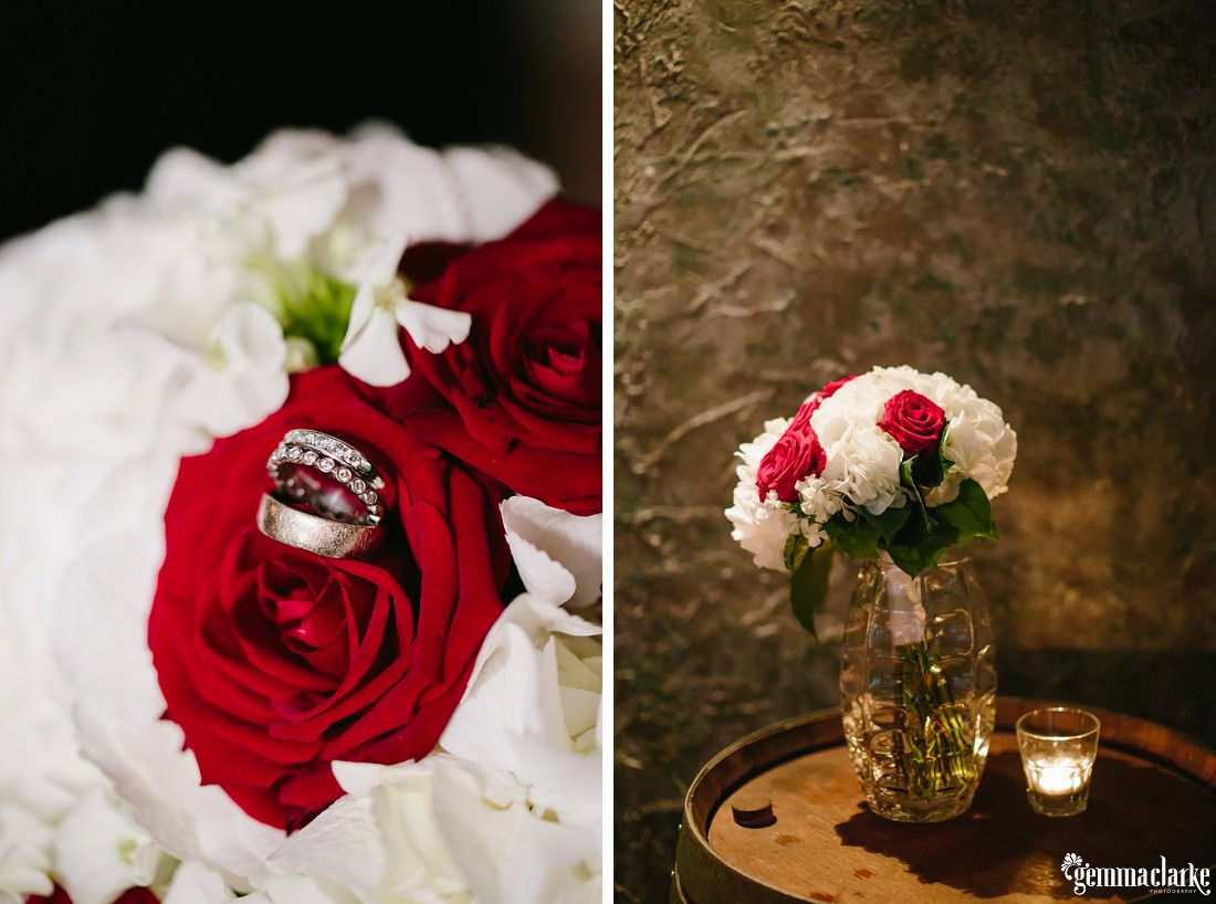 A bride and groom's rings on roses in a glass vase next to a candle in a small glass