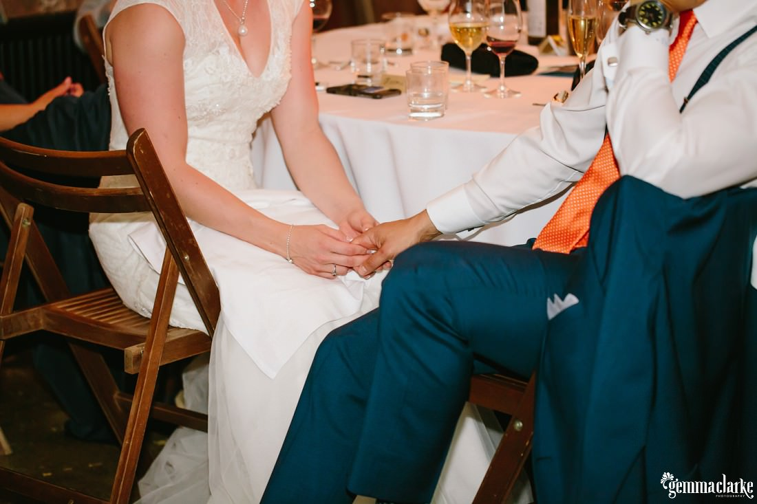A bride and groom seated at their reception holding hands