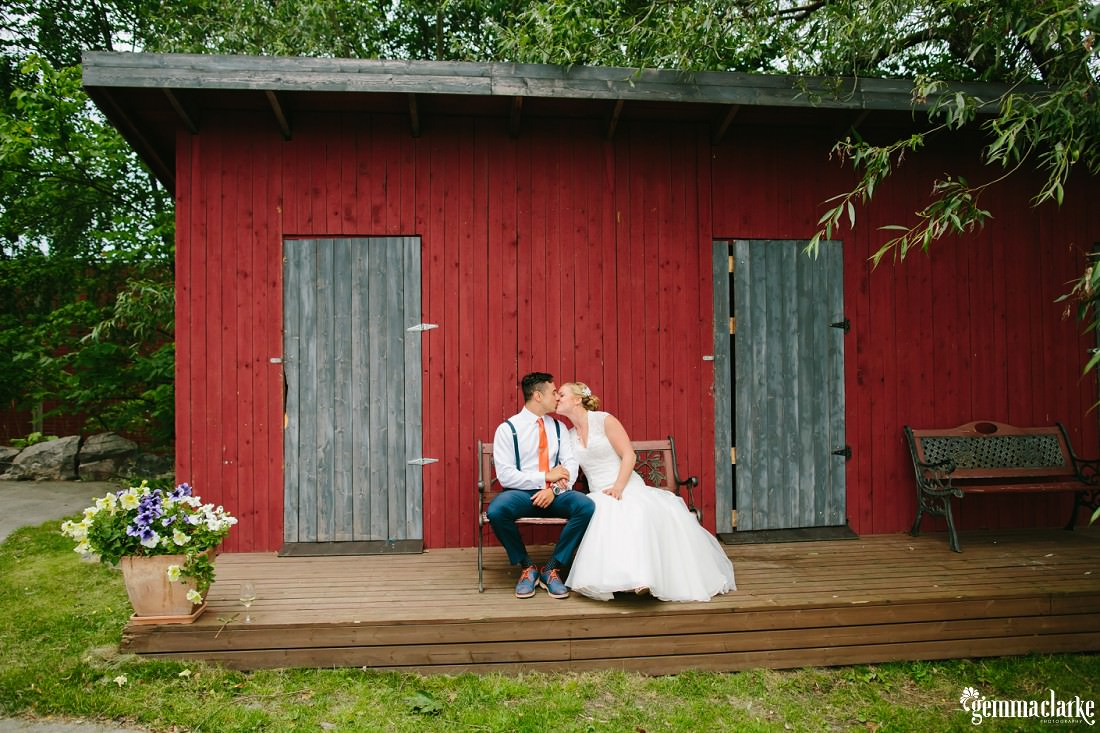A bride and groom kissing on a wooden seat in front of a red wooden building