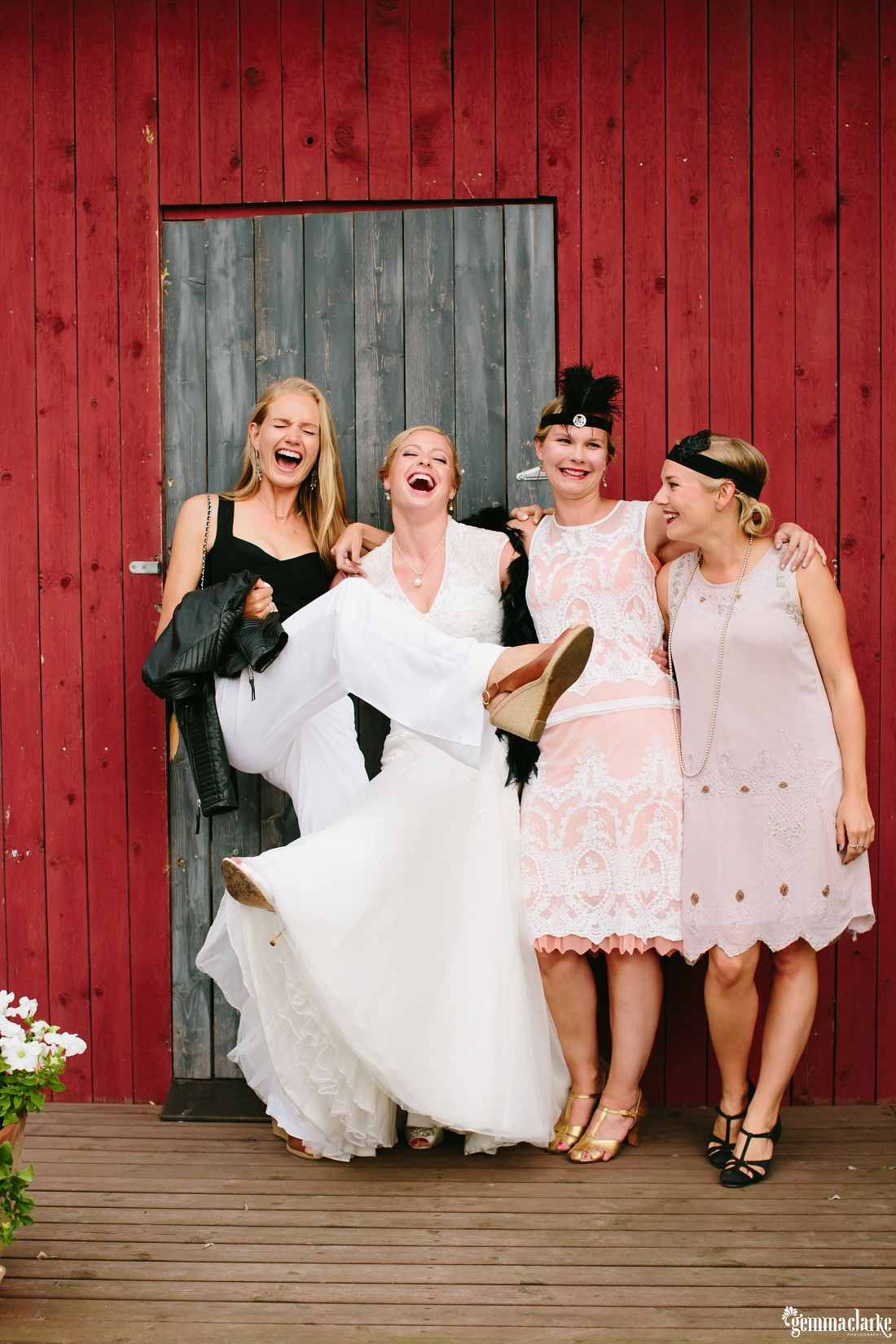 A bride posing with some of her guests in front of a red wooden building