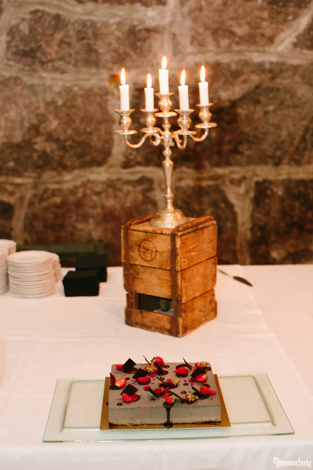 A wedding cake with strawberries and chocolate in front of a candelabra on a small wooden crate