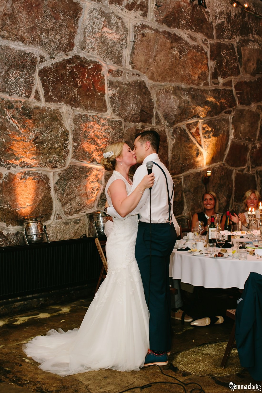 A groom kisses his bride at their wedding reception
