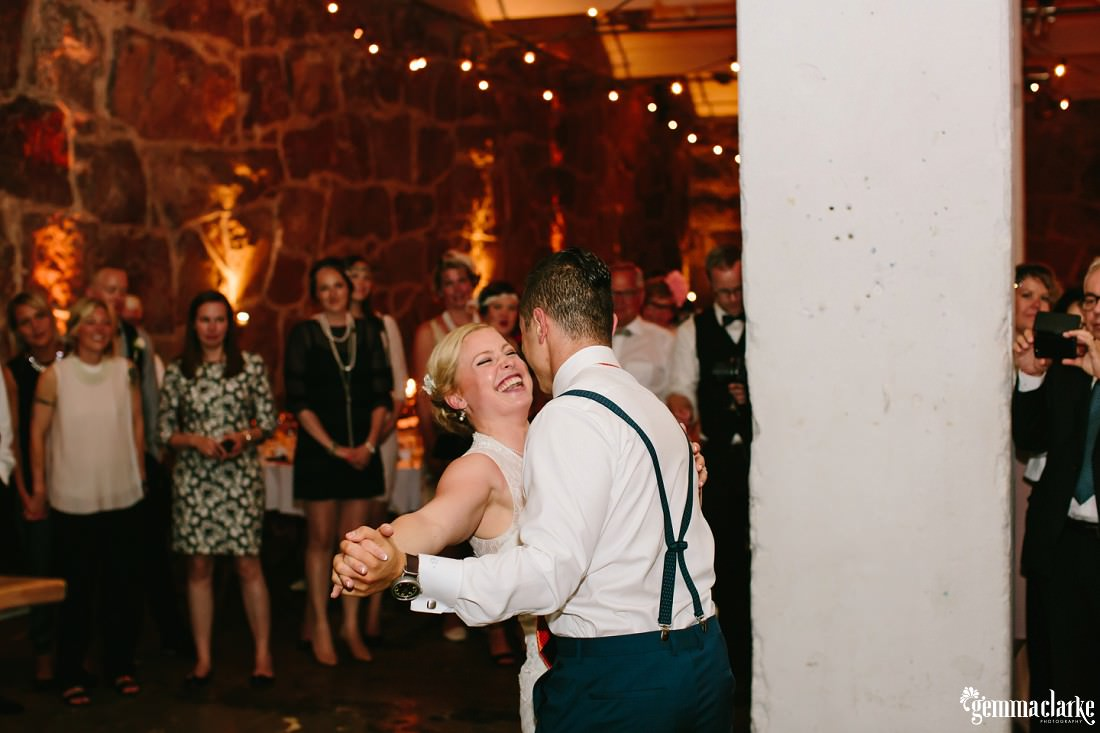 A smiling bride dancing with her groom