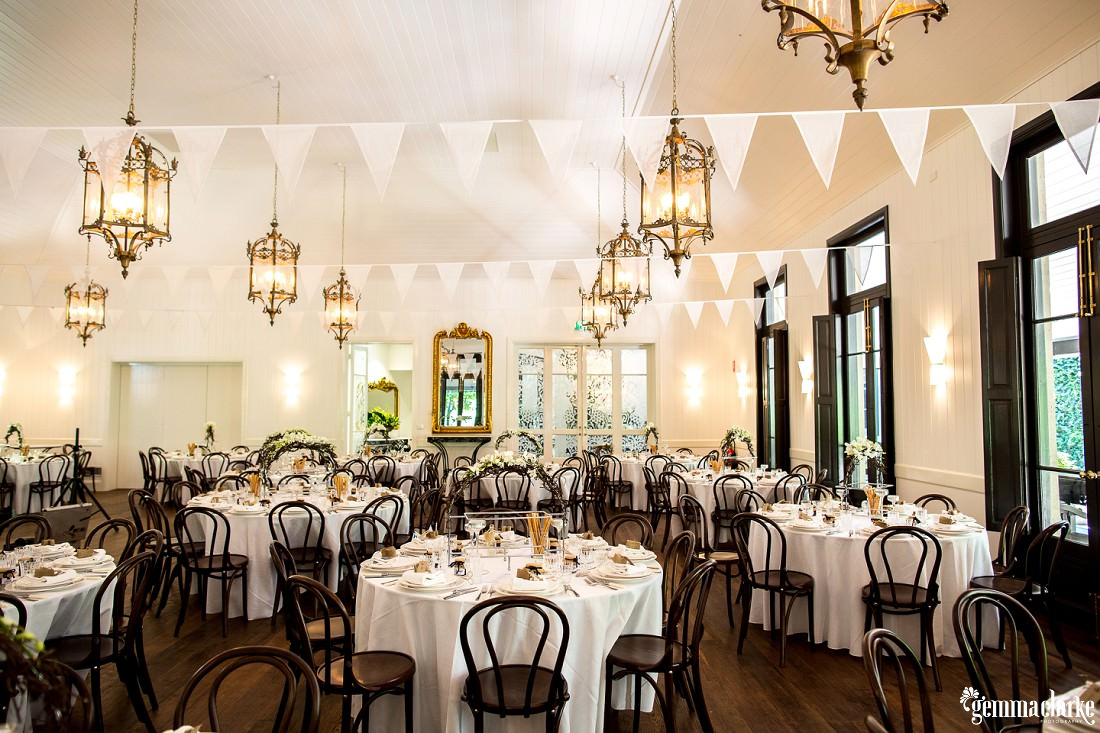 Reception setup with white tablecloths, wooden chairs, white bunting across the room - Jaspers Wedding