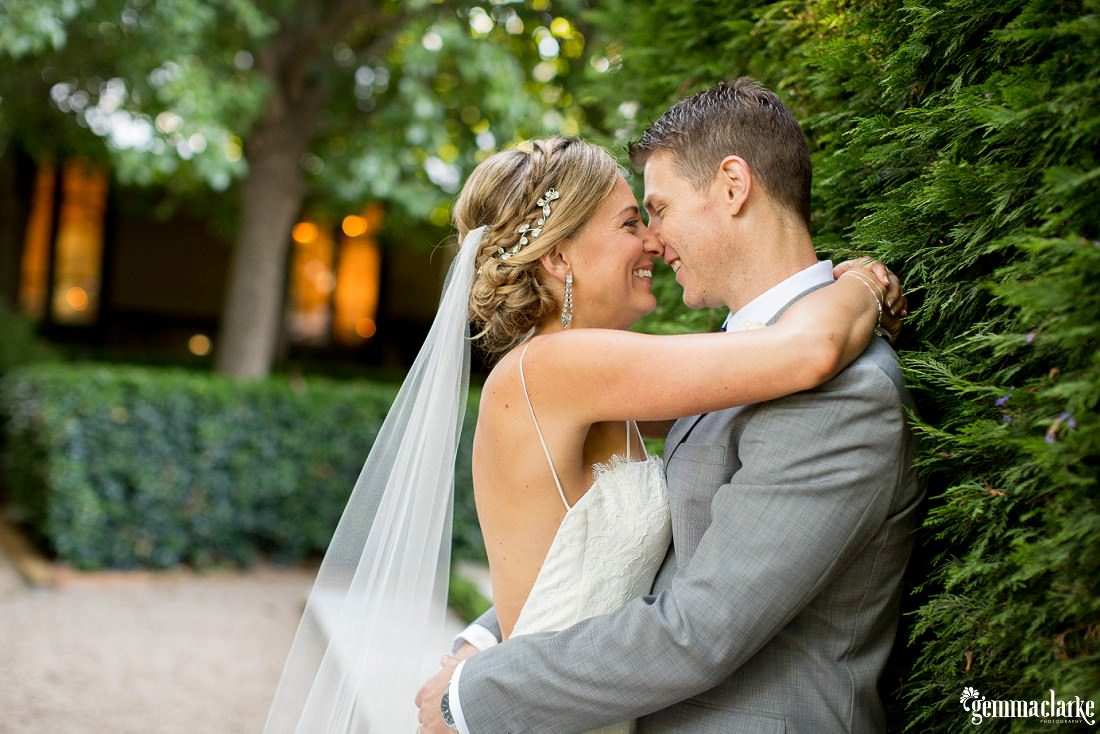 A smiling bride and groom embrace against a tall hedge - Jaspers Wedding