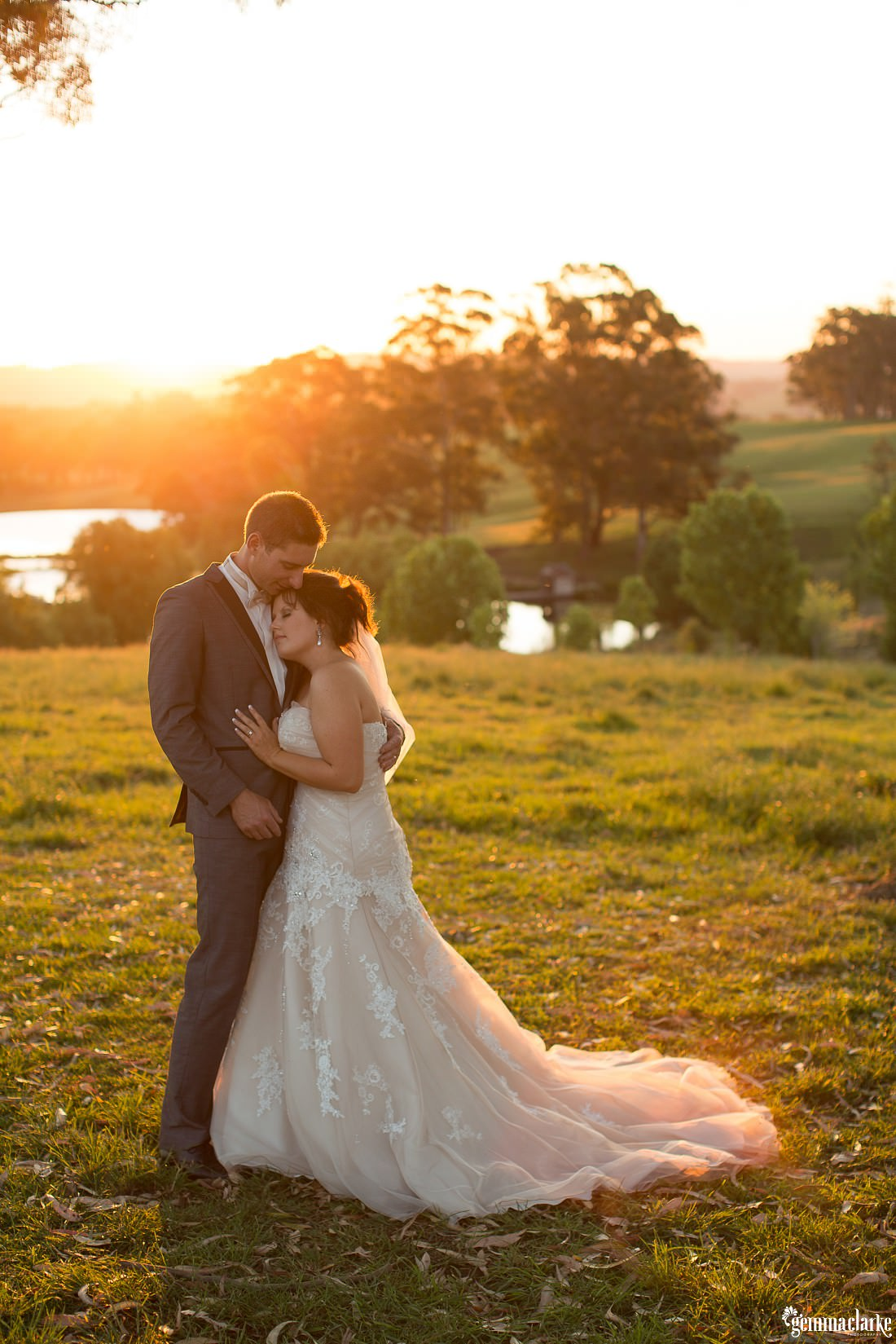 A bride leans her head against her groom's chest as the sun sets in the background - Mali Brae Farm Wedding