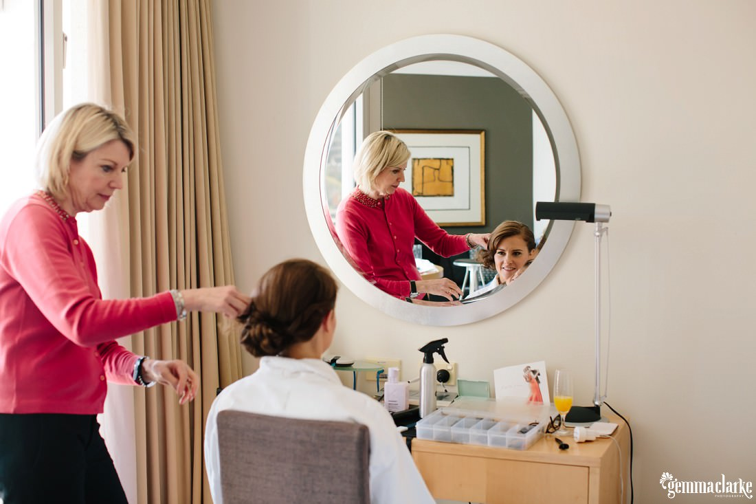 A bride sitting in front of a mirror having her hair done